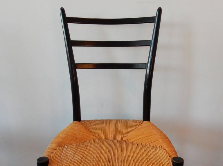 This is a fantastic set of five 'Spinetto' dining chairs by Italian manufacturer Chiavari. The ebonized wooden frames are in very good condition with some signs of age. All come with their floor rubbers. The wicker seats are in a very good condition