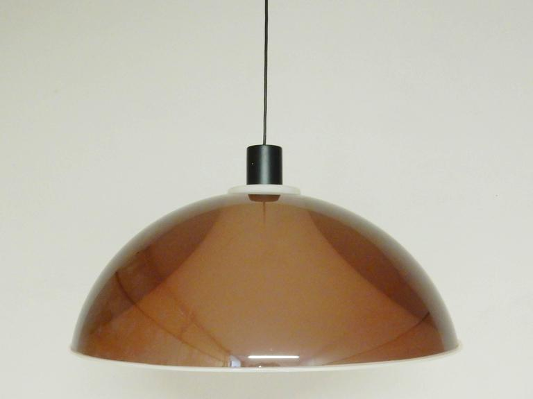 This is a very large plexiglass pendant light with a diameter of 55 cm. This model is more often seen as a floor lamp and attributed to Gino Sarfatti for Arteluce. A beautiful light that consist out of two shades on top of each other. When lit, a