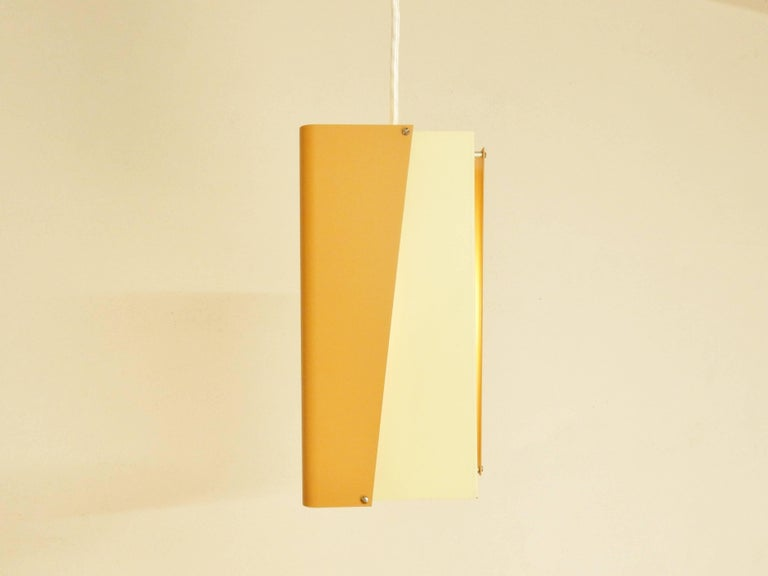 Orange and cream or off-white colored pendant lamp by Danish lighting manufacturer Lyfa. This light is a rare design that is not offered much. An arrangement of 4 in color lacquered folded metal sheets. The light is labelled with a sticker on the