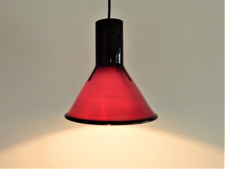 This mini P&T pendant lamp was designed by Michael Bang for Holmegaard in the 1970s. This Danish lamp is made of opaline glass and is black/aubergine on the outside and white on the inside. When lit, the lamp gives a partial warm red light. It is in