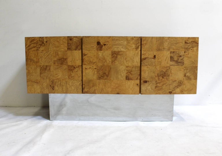 Milo Baughman for Thayer Coggin, circa 1970s. Beautiful, golden, burled wood, raised on chrome-plated steel plinth. Features two doors concealing four drawers and one large storage area with shelf. Has one small chip on top of front door and some