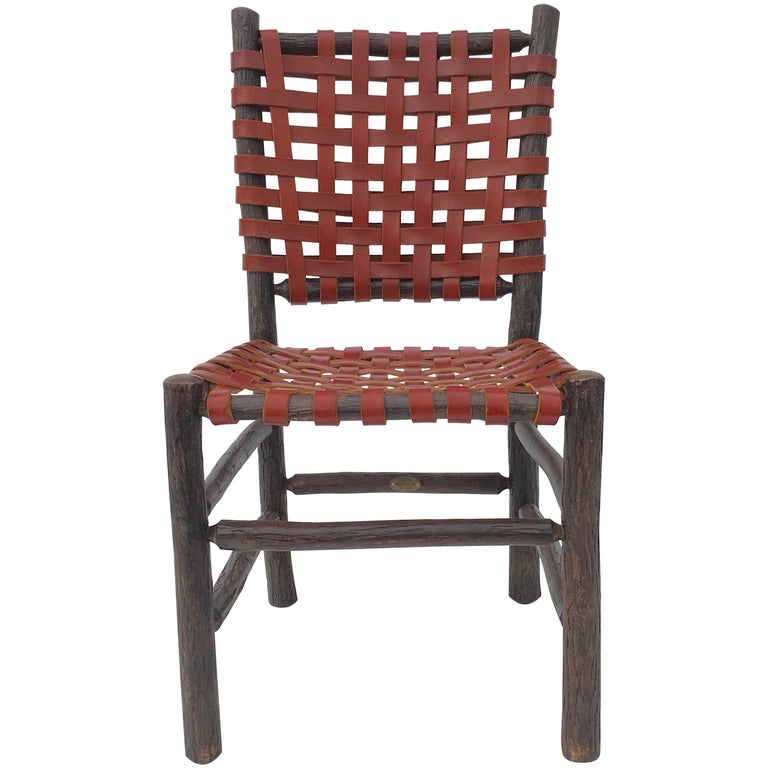 Twelve signed old hickory chairs with woven saddle leather seats and backs. More chairs available.