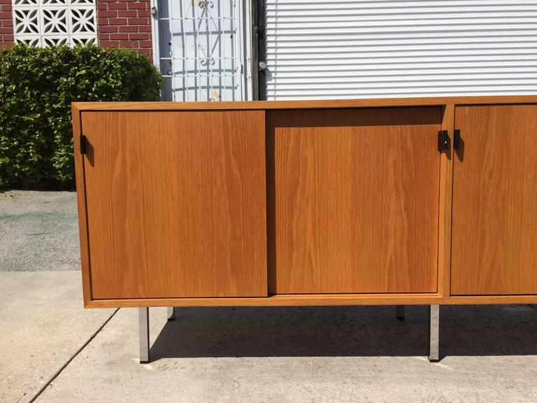 Credenza on six chrome legs, four sliding doors with black leather pulls. Behind the sliding doors are six shelves.