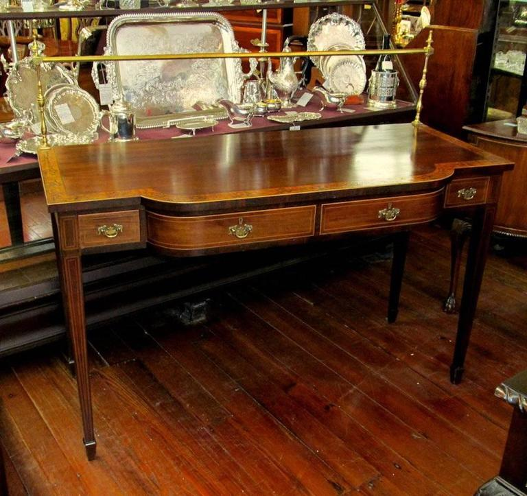 Superb quality antique English period Geo. IV inlaid mahogany shaped front Hepplewhite style huntboard server with fabulous marquetry inlaid crossbanded perimeter border and original brass gallery.