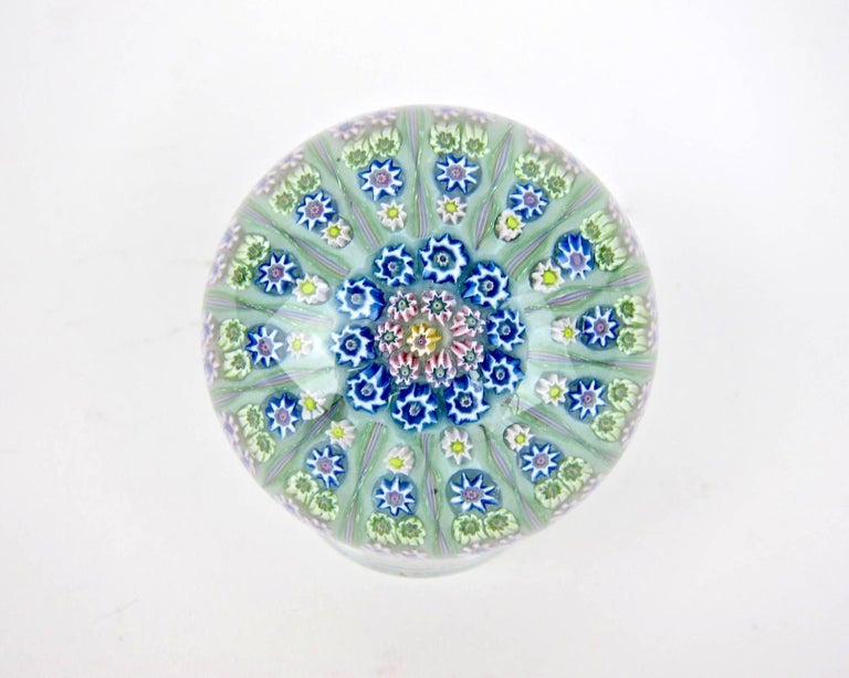 A vintage millefiori and twist art glass paperweight, handcrafted in Crieff, Scotland at Perthshire Paperweights, Ltd., circa 1969-1970.  Designed in a 1-1-2-2 pattern of fine millefiori canes separated by 14 spokes radiating from two rows of