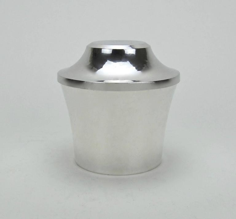 A sleek sterling silver covered box from the Art Deco period by Marie Zimmermann (1879-1972), a noted American silversmith, jeweler and designer active during the opening decades of the 20th century. The vessel comes from the artist's estate, dating