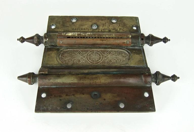 An unusually large Eastlake era antique double acting door hinge in heavy cast bronze/brass (weighs over 6.3 lb. / 2.85 kg) with distinctive steeple tip finials, circa 1880s. Due to its enormous size and elaborate Victorian design, this example of