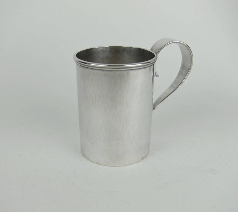 A handsome pair of Arts and Crafts era cups in heavy sterling silver with spot hammered surfaces and strap handles by noted American metalworker, jeweler and designer, Marie Zimmermann (1879-1972). Both mugs are fully marked and from the artist's