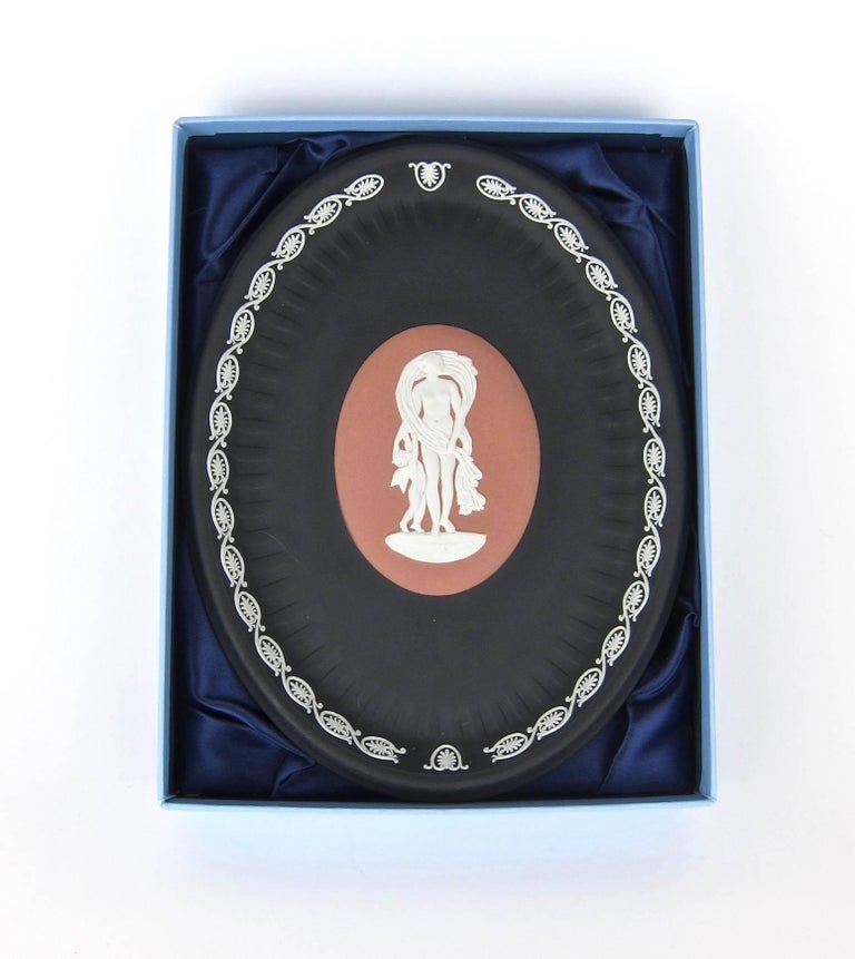 A handsome 'Venus and Cupid' oval tray with a satin lined and fitted box, signed by Lord Wedgwood in 2002. The tray is decorated in the Classical style with white bas relief jasper figures on an oval terra cotta central medallion, surrounded by