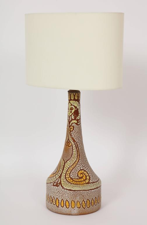 Midcentury accolay attributed yellow, orange, brown ceramic lamp, 1950 France with a face design Lovely ceramic lamp, circa 1950s. 16 inches to top of pottery, 25.5 inches to top with shade, 7 inches diameter at base, wired for US.