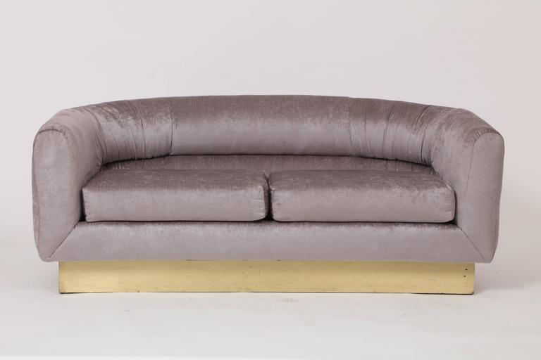 Milo Baughman for Thayer Coggin attributed velvet platinum grey settee sofa on brass plinth, 1980 Newly upholstered Milo Baughman settee on brass plinth Crescent shape  Measures: 61 inches wide 32 inches deep 24 inches height.