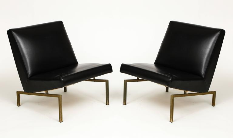 Joseph Andre Motte black tempo pair lounge chairs brass Mid-Century, France.  Faux leather black chairs with brass base lounge chairs byJoseph Andre Motte. Sculptural shape. Edited by Steiner.  Measures: Height: 27. Width: 22.5. Depth: 27. Seat