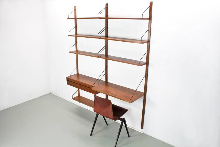 Original Danish wall unit, model Royal, designed by Poul Cadovius in the 1950s for Cado, Denmark.   This listed unit was produced by Cado in Denmark in the 1960s. The elements features a lovely quality teak veneer with brown uprights of 2 meter.