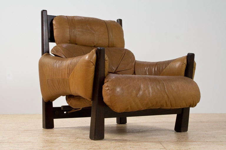 The dark asymmetrical ash wooden legs, the upholstered camel colored leather seating and armrests and the rope construction of the back seating, all refer to the iconic Brazilian modern and almost Brutalist designs of Percival Lafer. At present we