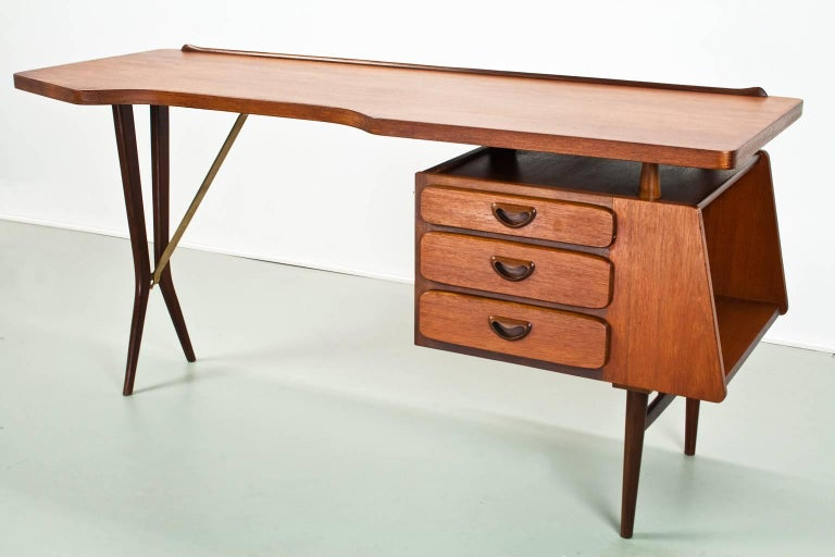Original and fully restored iconic Mid-Century Modern desk with floating tabletop and brass detailed arm on the black lacquered wooden legs. In absolutely excellent condition. 