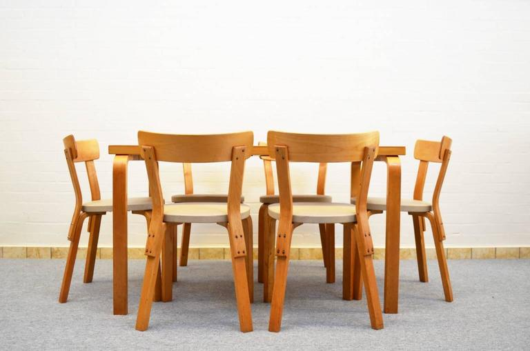 Iconic dining set from Finnish designer and architect Alvar Aalto. De set consists of a table (model 82A) and six chairs (model 69) with vinyl upholstery. All original from first owner.