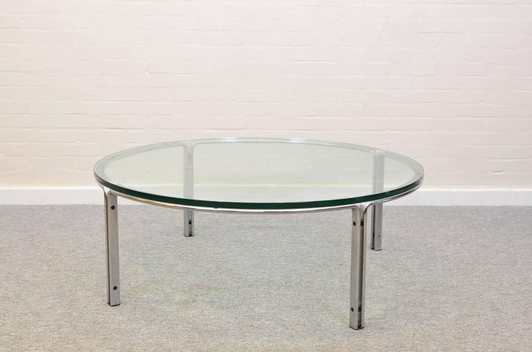 The table features a chromed steel base with a heavy 19 mm thick glass tabletop. The tabletop has some light scratches.