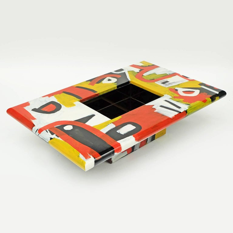 The studio coffee table is a bespoke piece created by the artist Alan Fears.   The table features a hand-painted free-form primative tribal design.  Central tinted mirror storage.   Measure: H 33cm x L 137cm x W 87cm.