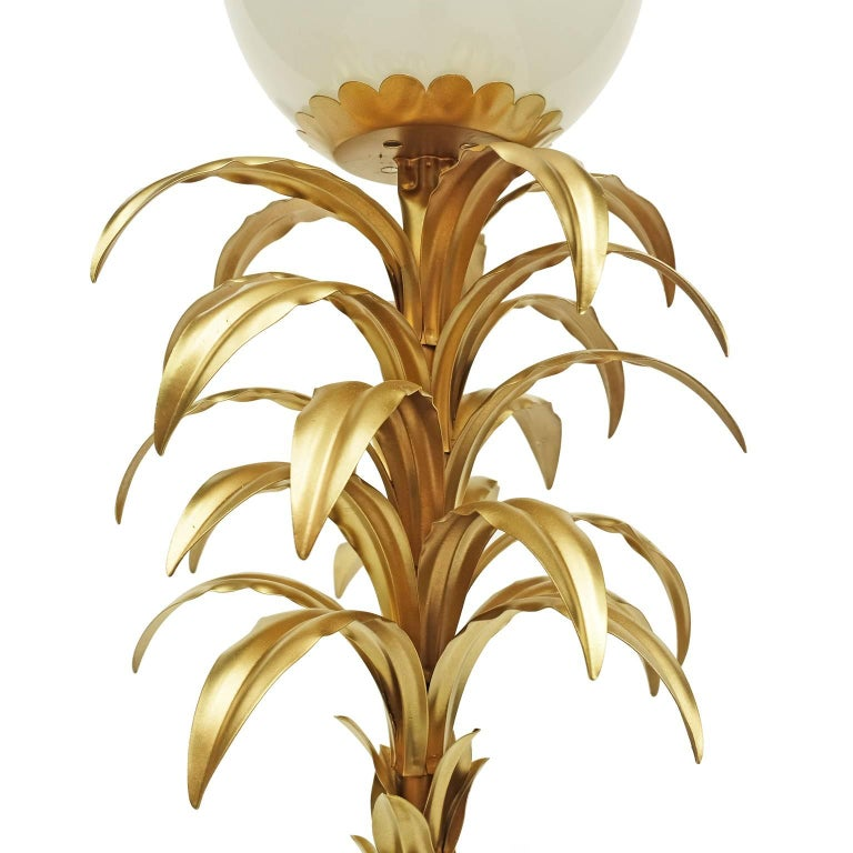 Floor lamp designed and manufactured in France, 1970s  Decorative gold metal palm leaf design with an opaque glass spherical shade.  Foot switch.  .