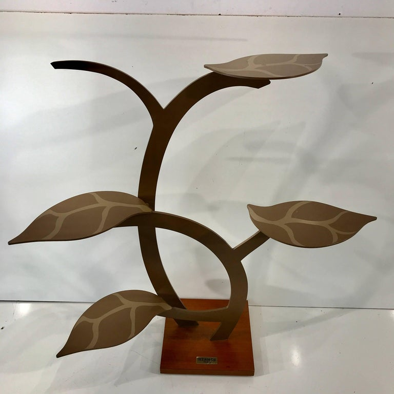Vintage Hermes display stand, this remarkable tree is made of enameled and polychromed metal mounted on a square wood base. The leaves serve as display surfaces and are removable. Each leaf measures 8.5