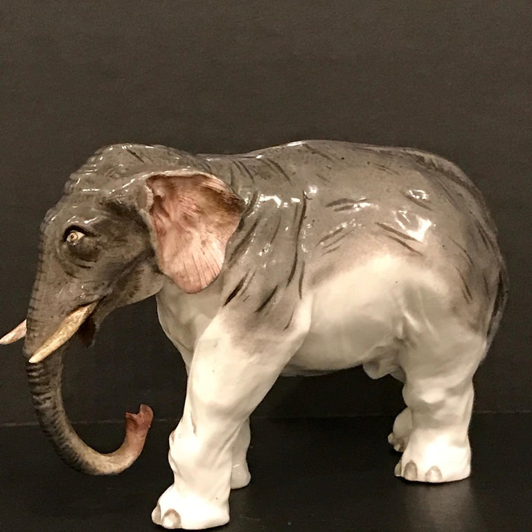 Meissen model of an elephant, standing four square with raised trunk, crossed swords with dots mark.