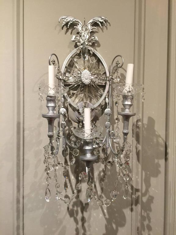 Gorgeous pair of neoclassical wall sconces. Each one of large-scale, silvered metal, and fitted with three lights and cascading crystal. Two pair of sconces are available.