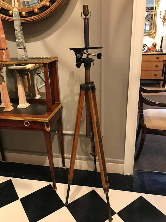 Antique movie camera tripod stand, now as a lamp, similar form as a surveyors tripod, made of carved maple and extendable brass legs. Complete with custom gilt and gun metal shade measuring 12