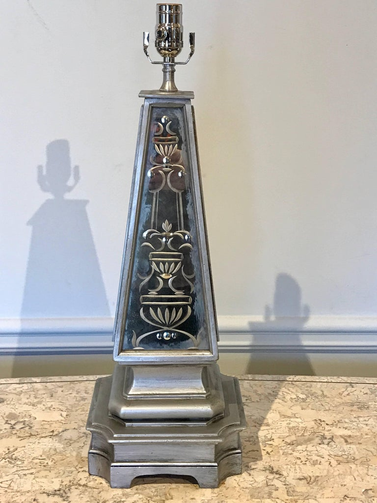 Pair of silvered and engraved mirror obelisk lamps, each one of typical form with dual inset (mirrored front and back) neoclassical engraved mirrored panels. Measures 20