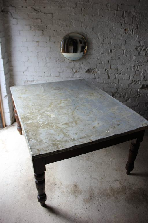 Of great character, the unusual Victorian stained pine kitchen or farmhouse table, later used as a preparation or work table, of good size and colour, having a rectangular top, later being covered by tacked on zinc, the whole on turned legs and