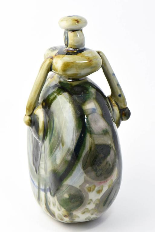 Ceramic figurine in the shape of a woman with green, blue, white and beige mottled glaze. Signed on base, but not fully legible.