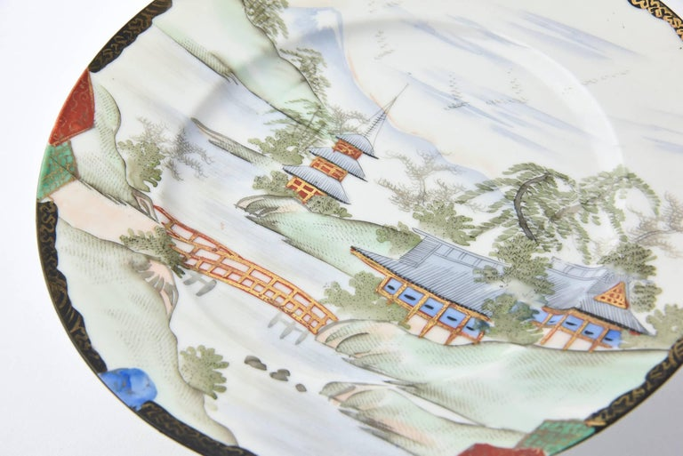 Pair of Japanese compotes hand-painted with Mount Fuji in the background of a classic Japanese village design. The village features a picturesque brook with a textured bridge accented by hidden pagodas in classic Japanese garden motif. The backs are