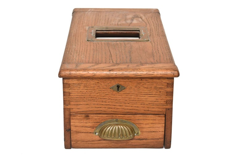 Victorian ballot box   This Victorian ballot box is an excellent example of a mid-19th century Wooden ballot box with brass hardware. Ballots were paper in that era and a roll of paper in contained inside the box. There is a drawer in the bottom (a