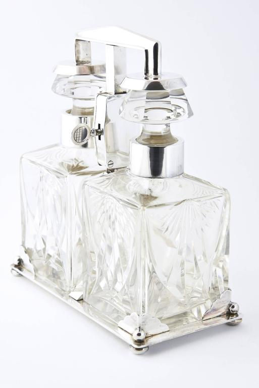 An Art Deco tantalus in a WMF silver plated frame, circa 1920, two squat rectangular cut-glass decanters with silvered mounts and having faceted mushroom style stoppers, enclosed in a lockable frame, marked WMF.