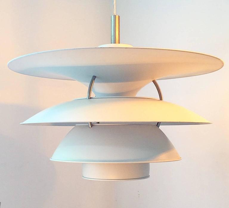 This is the large version of the ceiling lamp designed by Poul Henningensen for the exhibition hall Charlottenborg in Copenhagen in 1979 and manufactured by Louis Poulsen.  The famous shade system PH 6,5 - 6 by Poul Henningsen ensures a beautiful