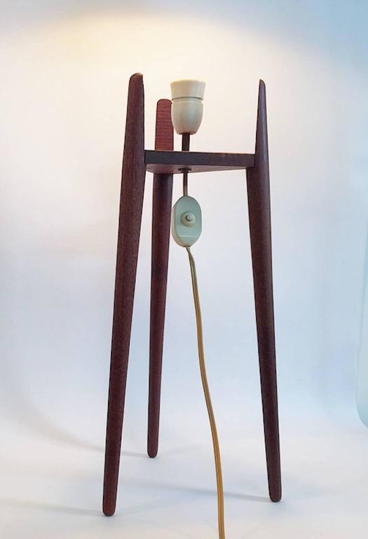 Amazing floor lamp designed in the 1950s with lovely details. The tripod base holds the bulb holder and the original shade.   The shade is made of celluloid with a woven structure and has beautiful brass details at the bottom and the top.   The