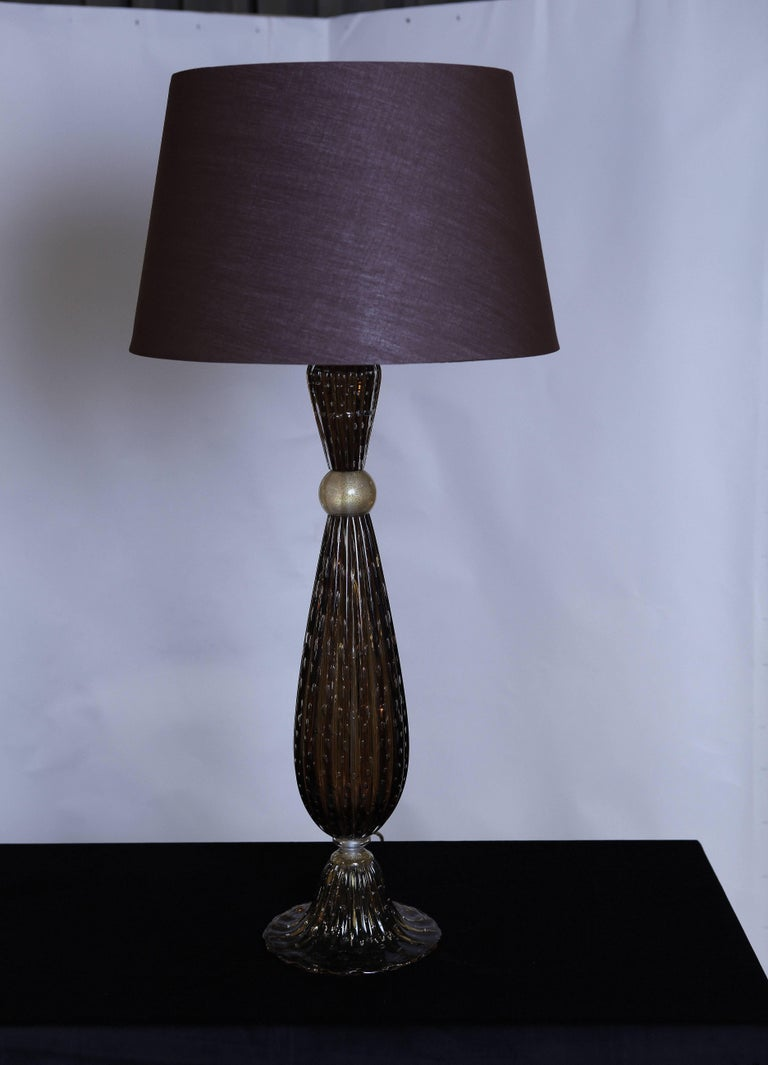 A beautiful pair of Murano glass table lamps in dark amber color.