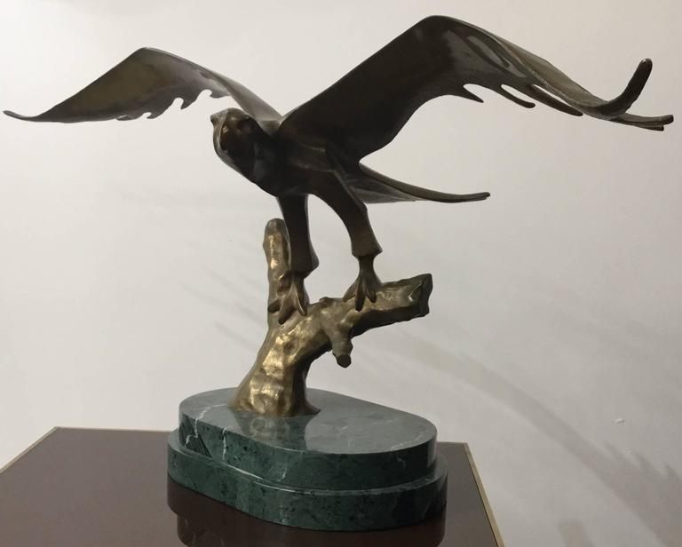 A modern sculpture of an eagle about to take off in bronze-mounted on a green marble base finely detailed, with foundry marks.