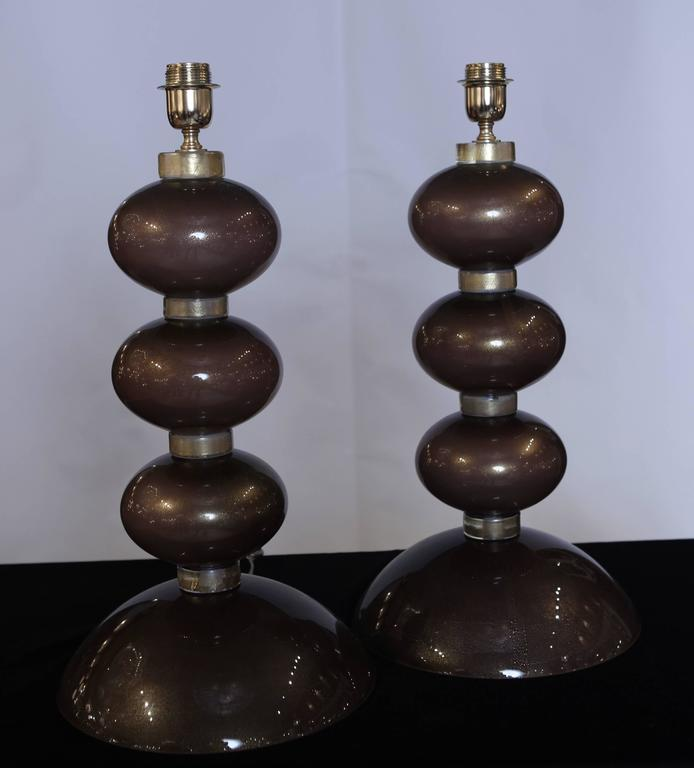 The table lamps are made up of three oval bronzed Murano glass pieces sitting on a large base. The components are fused to Murano glass discs with gold inclusion.