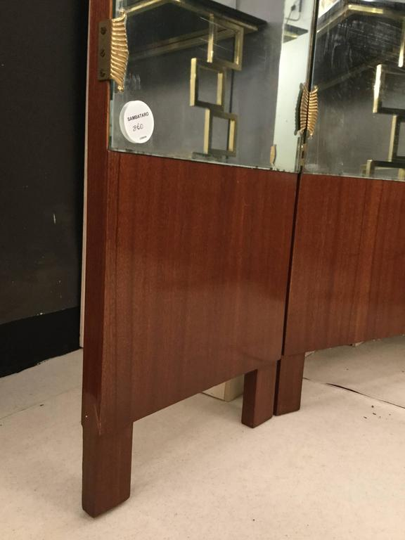 A beautiful Italian screen in walnut and three mirrored panels.