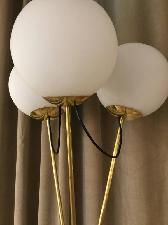 A pair of Italian designed floor lamps three spherical glass shades on brass tripod legs in the style of Stilnovo.
