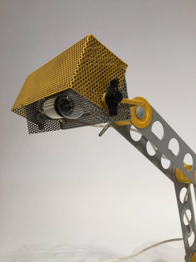 An Italian designed table or desk lamp post modern in the style of Ettore Sottsass in steel with perforated yellow shade in the bright Memphis colors, 1980.