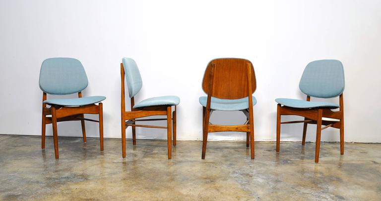 Rare and early set of Mid-Century teak dining chairs with floating seats and curved backrests, typical of Finn Juhl's designs. The frames are in original condition with rich patina and have been newly fitted with a light turquoise fabric. The chairs