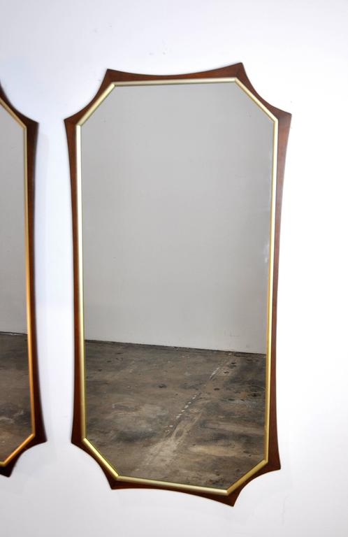 An eye-catching pair of vintage Mid-Century mirrors dating from the 1960s. Each large mirror features an octagonal walnut frame with brass toned trim. A unique find that will instantly decorate any room.