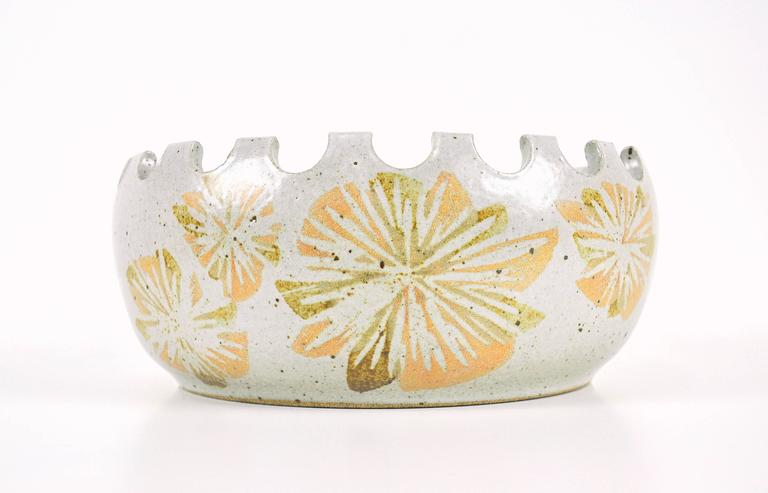A rare Mid-Century Modern Robert Maxwell and David Cressey for Earthgender hand-thrown art pottery off-white centerpiece bowl. The large, round and deep ceramic dish features a crenellated rim and abstract green, burnt orange / ochre floral
