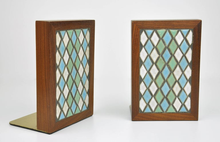 Colorful and decorative pair of Mid-Century Modern walnut, stoneware ceramic tile and brass model TBE1-21 book ends, dating from the late 1950s. The fronts feature a diamond pattern of turquoise / light blue, pastel green and off-white / cream tiles