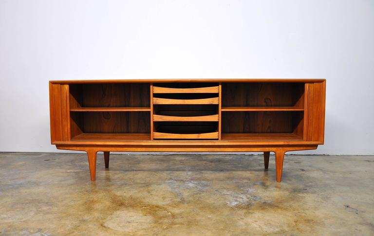 This nearly 7 foot long Mid-Century teak sideboard features two individual sliding tambour doors that allow unobstructed access to the interior. The door fronts have sculpted teak handles and grain patterns that are quite striking. The interior