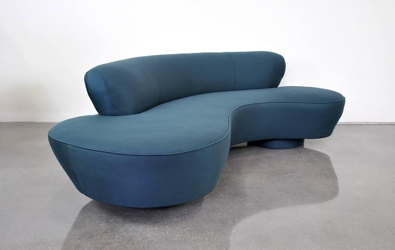 Iconic Mid-Century Modern biomorphic sofa by design legend Vladimir Kagan for Directional reupholstered in an amazing deep blue Maharam fabric. Features a kidney or cloud shape with round upholstered bases and Lucite fin. The dark blue wool fabric