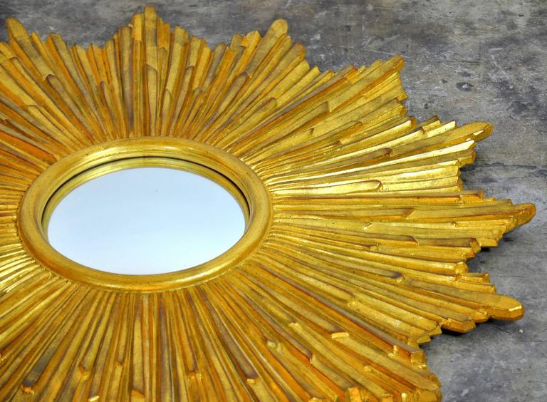 A lovely French or Italian style handcrafted gilt starburst wall mirror. The round convex mirror centres a wood frame beautifully shaped as beams of light. The frame has a hand-laid antique gold leaf finish, a 15 step process that takes around two