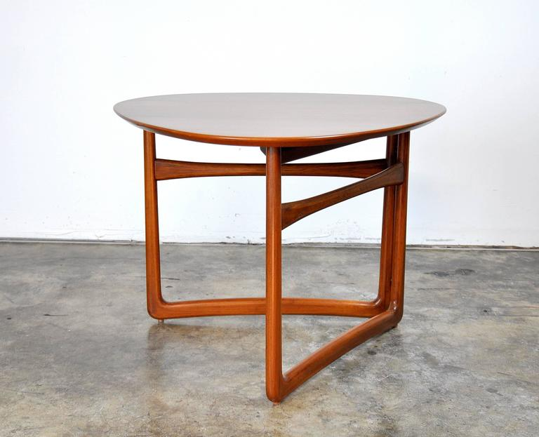 Gorgeous Mid-Century Danish Modern solid teak occasional table, model FD 18/57 designed by Peter Hvidt and Orla Mølgaard-Nielsen and manufactured by France and Daverkosen (pre France and Son) in the 1950s. The triangular top rests on a sculptural