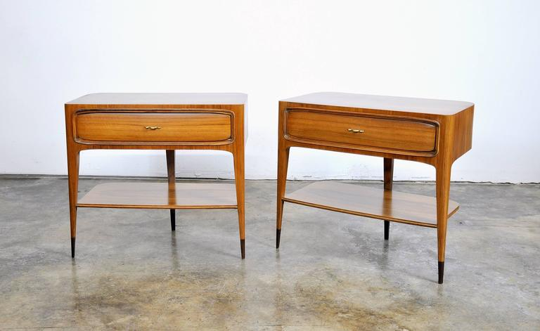 Exquisite and elegant pair of Italian Mid-Century Modern side, end or bedside tables made in Italy in the 1950s and attributed to Paolo Buffa. Professionally refinished, each demilune night stand features a curved back, solid brass zig zag pulls and